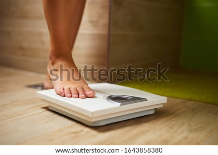 Woman weighing herself on weight scale in bathroom Photo stock ©
