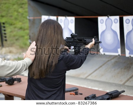 Woman who is shooting a fully automatic rifle at targets