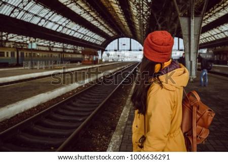 woman wiating for train on railway station in hat Zdjęcia stock ©