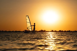 Woman windsurfer silhouette at lake sunset. Beautiful beach landscape. Summer water sports activities, recreation and travel concept