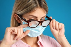Woman wiping foggy glasses caused by wearing disposable mask on blue background, closeup. Protective measure during coronavirus pandemic