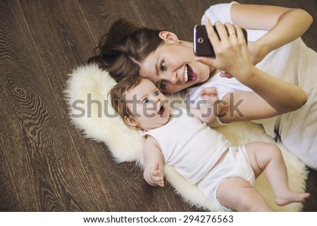 Woman with a baby doing a selfie lying on wooden floor