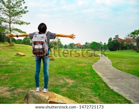Woman with a backpack standing on a rock arms up and enjoying the moment of fresh air in the forest (ozone therapy)