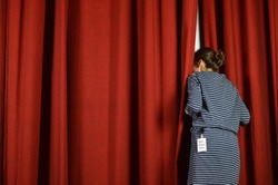 woman with a backstage pass looking behind the red curtains on a stage