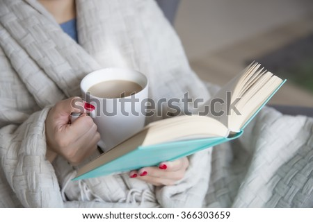 woman with a book and cup of hot drink #366303659