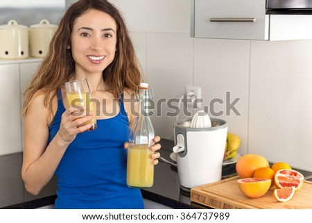 Woman with a bottle of fruit juice and fresh fruits