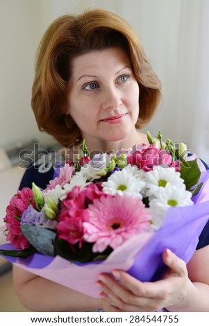 Woman with a bouquet of a flowers in the room #284544755