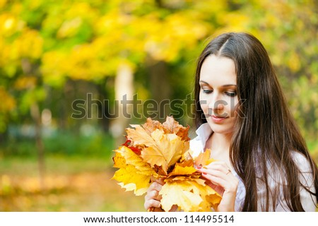 woman with a bouquet of autumn leaves