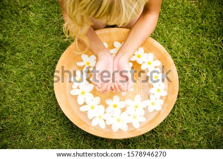 Woman with a bowl of floating frangipani in a tropical setting.