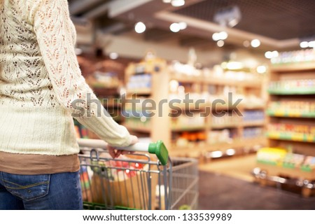 Woman with a cart in a store
