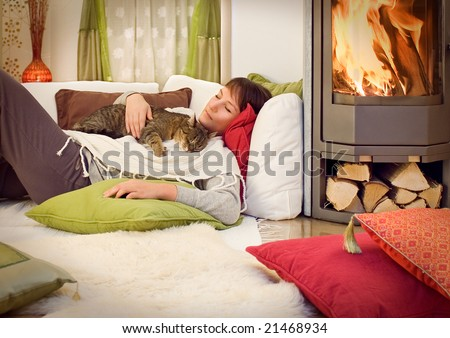 woman with a cat relaxing beside a fireplace. - stock photo