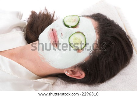 Woman with a claymask on her face and cucumber on her eyelids