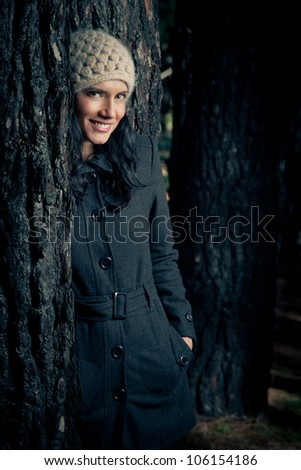 Woman with a coat and beany standing in a forest - stock photo