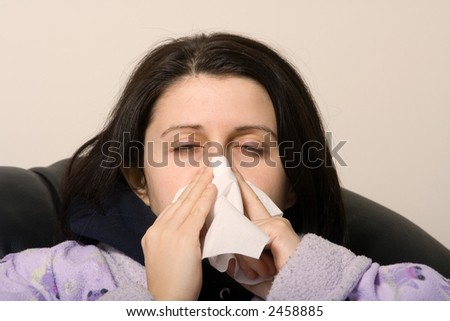 woman with a cold blowing her nose with a tissue - stock photo