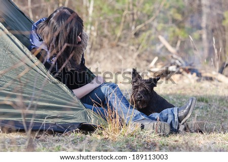 Woman with a dog resting at camp in the forest