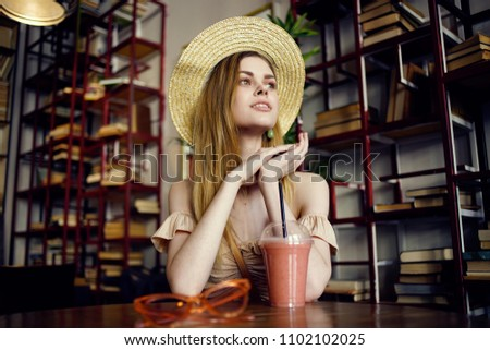 woman with a drink at the table and books in the background                            #1102102025