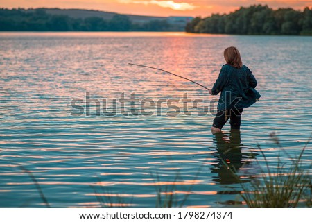 Woman with a fishing rod fishing on the lake on a summer evening