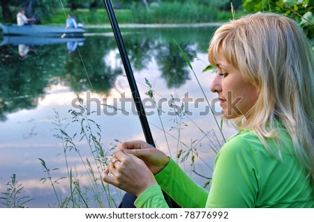 Woman with a fishing tackle fishes on the river
