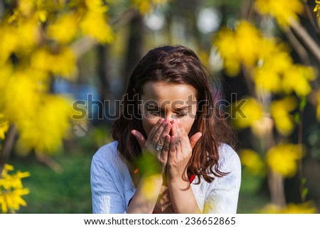Woman with a flu or an allergy is sneezing while standing outside, in a park