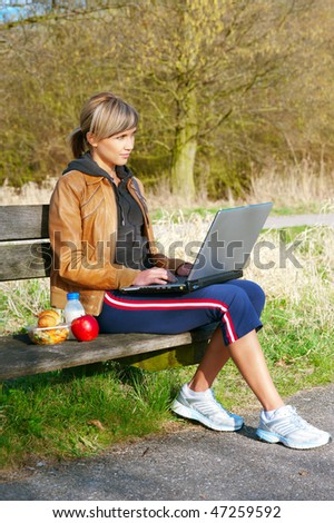 Woman with a laptop computer sitting outdoors on a bench.
