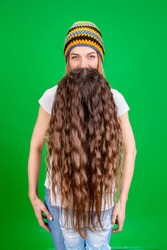 woman with a long beard and a hat in the studio on a green background