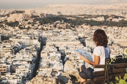 woman with a map sitting on Lycabettus Hill, the highest point in the city overlooking Athens with the Acropolis - world traveller