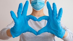 Woman with a medical mask and hands in latex glove shows the symbol of the heart. Doctor for the heart. Love to our pancreas. Love our medical professionals.