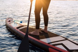 woman with a paddle on the blackboard. legs of a slender girl on stand up paddle board.