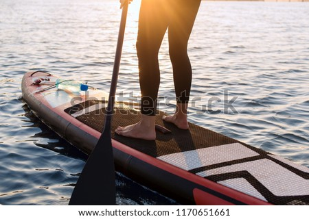 woman with a paddle on the blackboard. legs of a slender girl on stand up paddle board. #1170651661