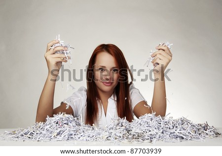 woman with a pile of shredded paper in front of her on her desk