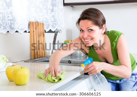 Woman with a rag and clear bottle with cleaning substance is cleaning kitchen furniture from dust and dirt