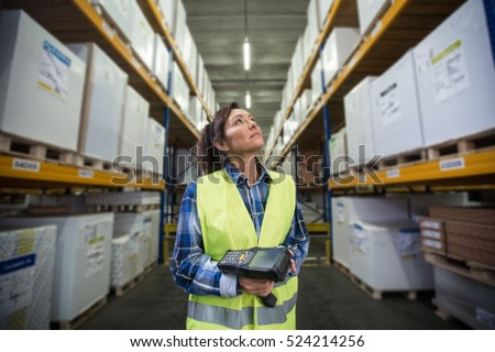 Woman with a scanner in her hands is checking inventory levels in a warehouse. First in first out, Last in last out, just in time delivery concept photo.