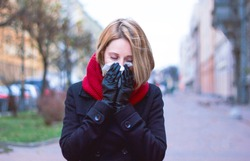 Woman with a scarf in her hands. the sick girl blows her nose in handkerchief. Seasonal colds and flu on a cloudy day. Sad blonde sneezes, outdoors or outside. On the street of the city, allergy.