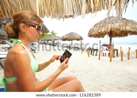 Woman with a smartphone on the beach. Vacation. - stock photo