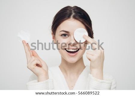 woman with a sponge blue background cotton pad problem skin