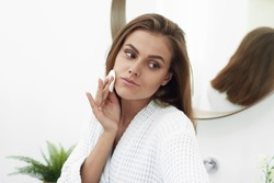 Woman with a sponge cotton pad problem skin. A picture of a happy girl cleaning her face with cotton pads over bathroom. Beautiful Face of Young Woman with Clean Fresh Skin
