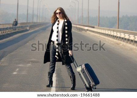 Woman with a suitcase standing on traffic line