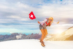 Woman with a Swiss flag on Titlis cliff in a snow storm. Top of Titlis mountain in the Uri Alps at 3028 meters in cantons of Obwalden and Bern, Switzerland, Europe. Summer season.
