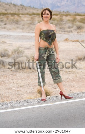 Woman with a sword in fatigues standing guard on a desert road