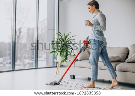 Woman with accumulator vacuum cleaner drinking coffee Foto stock ©
