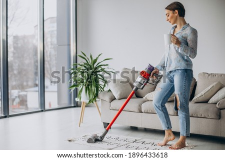 Woman with accumulator vacuum cleaner drinking coffee Stockfoto ©