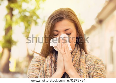 Woman with allergy symptoms blowing nose ストックフォト ©