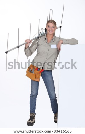 Woman with an aerial leaning against a blank poster - stock photo