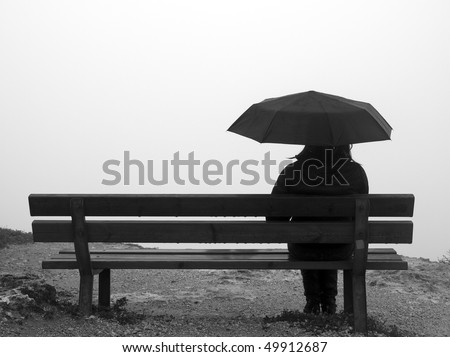 Woman with an umbrella sitting on a bench at a cliff edge