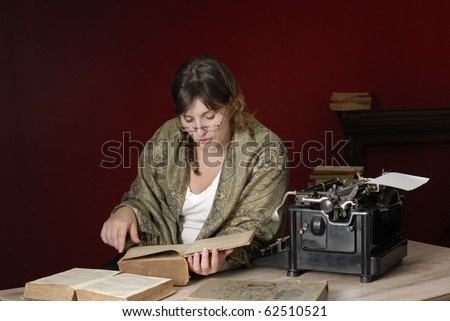 woman with antique typewriter reading very old books