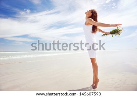 woman with arms out freedom girl on beach with flowers in summer