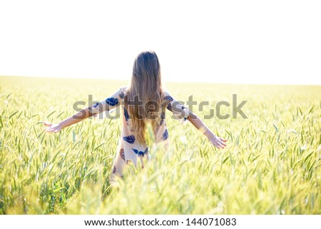 Woman in wheat field at sunny day