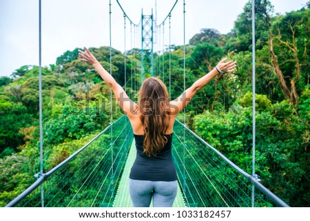 Woman with arms raised on hanging bridges of Costa Rica. #1033182457