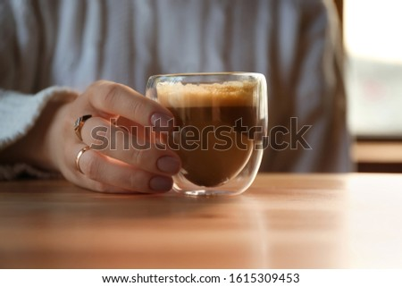 Woman with aromatic coffee at table in cafe, closeup