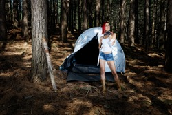 Woman with ax in hand in front of a tent in the woods
